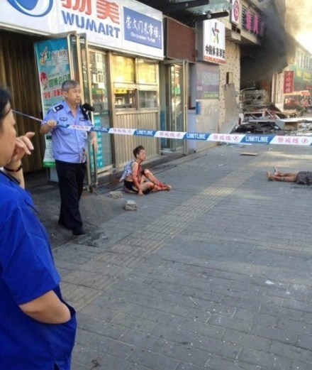 An injured man is sitting on the ground.