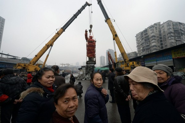 The Mao Zedong statue being hoisted up.