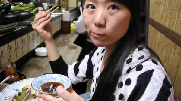 A Japanese woman eating fresh raw frog sashimi (sushi) in Japan.