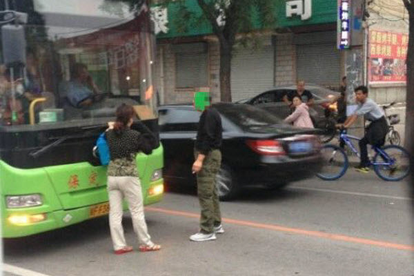 An elderly man and woman stand in front of a bus preventing it from leaving to protest the college students inside for not giving up their seats for the elderly in Baoding city, Hebei province of China.