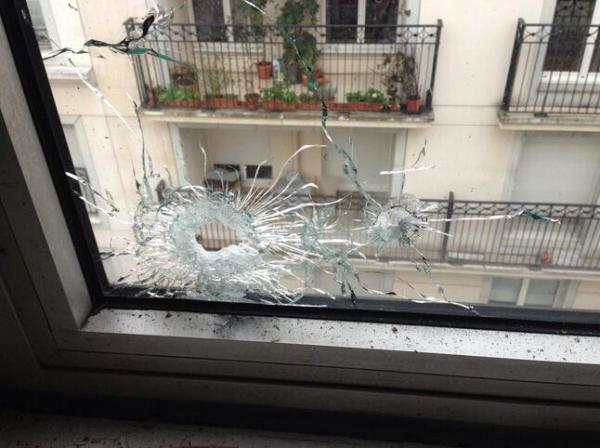 Photo is of a bullet hole in a window near the Charlie Hebdo headquarters office.
