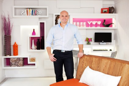 ATLANTA, GA: Licensed contractor Chip Wade stands in the transformed Atlanta, Georgia interior room of Tiffany and Andrew Pearson. The Pearson home renovation included a custom indoor/outdoor couch on a track, three dimensional wall unit, lounging cabañas, a grill area and game lawn, as seen on DIY Network's Elbow Room. (DIY Network, Elbow Room, Atlanta, home makeover, backyard, rotating couch, game area, grill, cabañas)