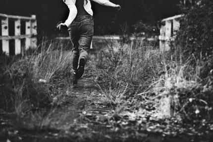 photographersydney/girl skipping at old bridge wearing denim overalls