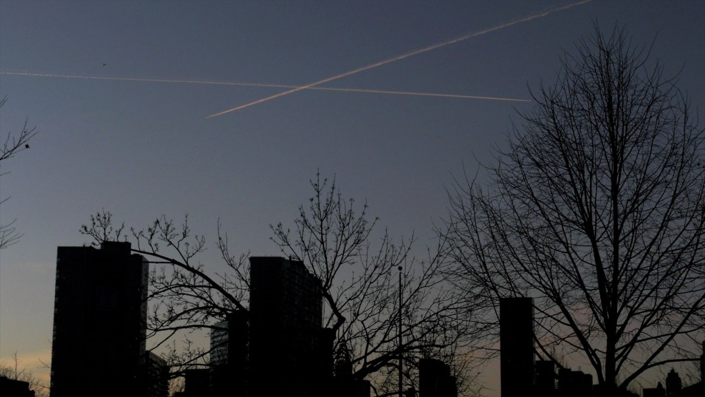Shadowed skyline of buildings and trees against a darkening sky at dusk. Two vapor trails cross each other overhead.