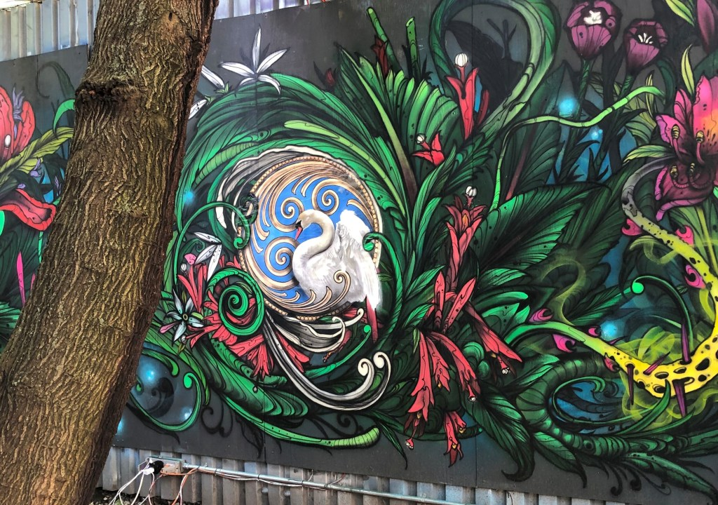 Mural painting of a swan surrounded by swirling flowers