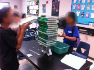 Students building a table out of chipboard and newspaper.