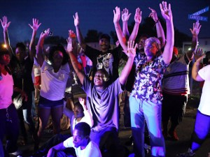 Protesters with hands in the air gesture...