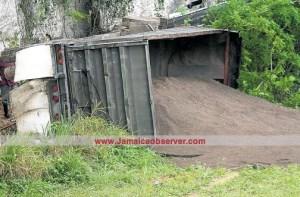 Toppled sand-laden truck