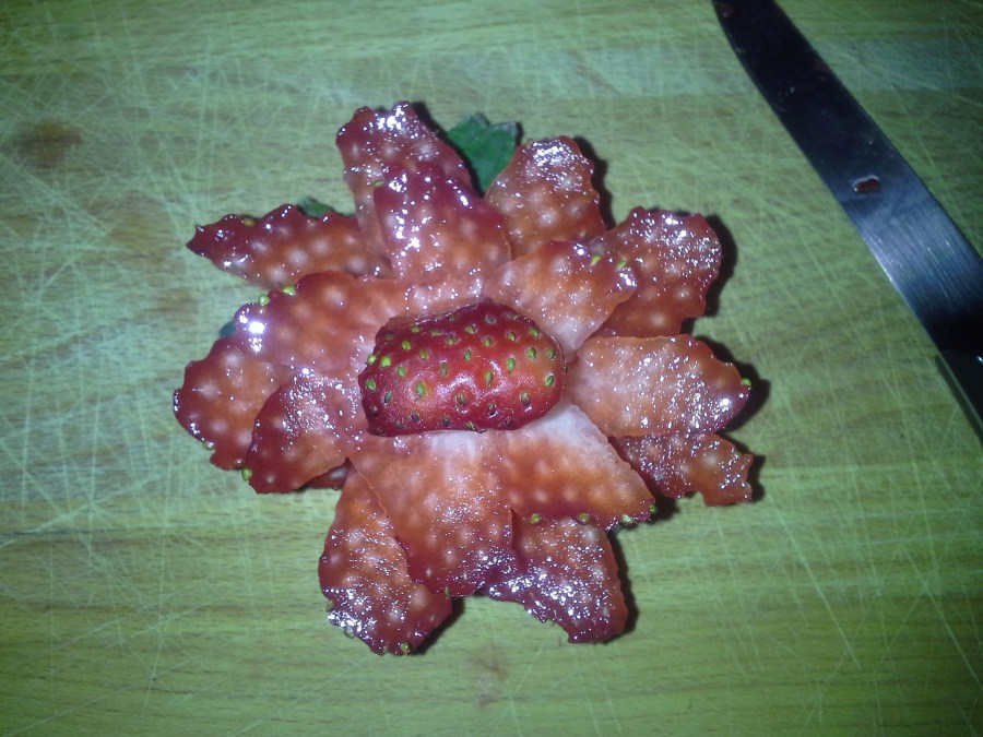 cutting a strawberry rose garnish