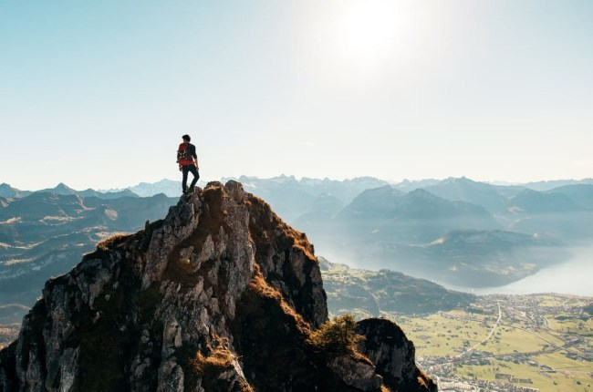 Man standing at the top of a mountain looking at the view