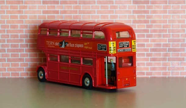 Red Bus Toy against a fake brick wall