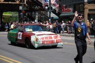 Bruce Parry waves in the parade as he is followed by CVO member Christopher LaFayelle driving a police car celebrating CVO and the Mexican American Veterans Association.