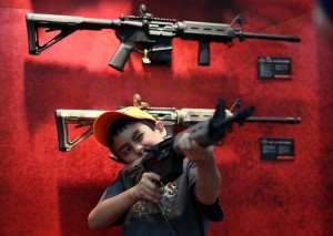 HOUSTON, TX - MAY 04:  An young attendee inspects an assault rifle during the 2013 NRA Annual Meeting and Exhibits at the George R. Brown Convention Center on May 4, 2013 in Houston, Texas.  More than 70,000 peope are expected to attend the NRA's 3-day annual meeting that features nearly 550 exhibitors, gun trade show and a political rally. The show runs from May 3-5.  (Photo by Justin Sullivan/Getty Images)