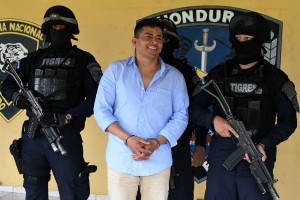 """Picture taken on August 20, 2017 showing Honduran drug trafficker Sergio Neftali Mejia Duarte, aka """"El Compa"""", being escorted by members of the Tigres Special Foreces following his arrest in Amarateca, 20 km north of Tegucigalpa. Mejia Duarte was sentenced on May 21, 2018 by a court in southern Florida, US, to life in prison after being found guilty of participating in an international drug trafficking organization. / AFP PHOTO / Orlando SIERRA"""