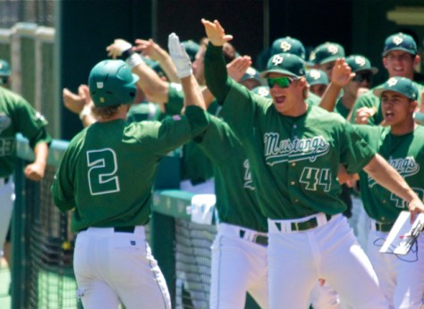 The dugout greets John Schuknecht after scoring. (Photo: Shotgun Spratling)