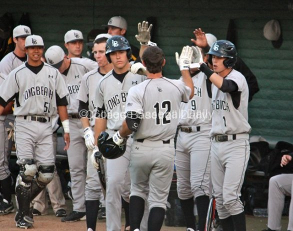 Brennan Metzger is greeted by the dugout after scoring.