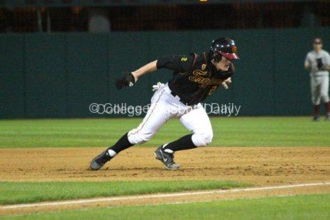 Adam Landecker dives back to first base.
