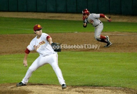 Kyle Davis pitches as a runner takes off.