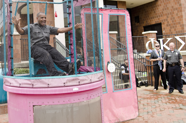 VCU police officer Jaime Rodriguez is dropped into a carnival-style tank after being dunked during the second annual Dunk-A-Cop fundraiser. Photo by Chris Conway