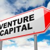 Venture Capital - Inscription on Red Road Sign on Sky Background.