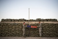 "Two airmen fold a flag during the retreat call at Camp Etchberger in what was once ""The Quiet Place."""