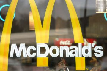 WILLOWBROOK, IL - NOVEMBER 11: A patron is seen through a window displaying McDonald's golden arches as she eats her meal at a McDonald's restaurant November 11, 2002 in Willowbrook, Illinois. The Oak Brook, Illinois-based company has announced that it will restructure its operations in four countries and close in three countries, shutting down approximately 175 underperforming restaurants in about 10 other countries and eliminating 400-600 positions to control costs and reallocate resources. McDonald's Corporation systemwide sales totaled $3.5 billion for October and $34.5 billion for the first ten months of 2002, up 3% and 2%, respectively in constant currencies. (Photo by Tim Boyle/Getty Images)