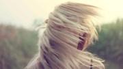 Garota loira com os cabelos ao vento cobrindo o rosto