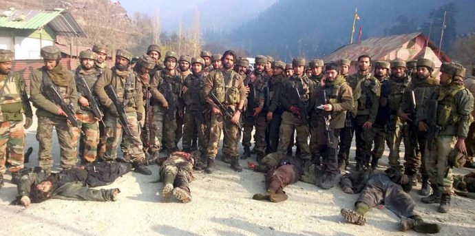 Uri: Army personnel stand near the dead bodies of militants who attacked Mohura army camp, in Uri on Saturday. PTI Photo(