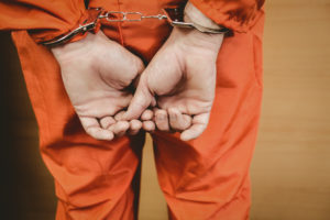 Hands of criminal with handcuffs in the court room