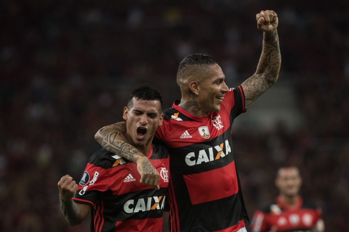 Brazil's Flamengo Miguel Trauco (L) celebrates with teammate Paolo Guerrero after scoring a second goal against Argentina's San Lorenzo during their Libertadores Cup football match at Maracana stadium in Rio de Janeiro, Brazil on March 8, 2017. / AFP PHOTO / Yasuyoshi Chiba