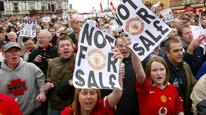 Manchester United fans protest, outside Old Trafford before the match, against the rumoured takeover of the club by American billionaire Malcolm Glazer