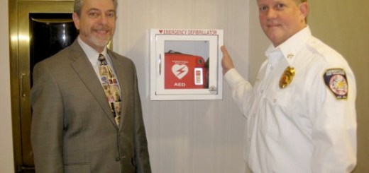 Kerry Green, Executive Director of the Hussey-Mayfield Public Library, and Steve Gilliam Division Chief of EMS for the Zionsville Fire Department, stand next to the automated external defibrillator and cabinet given to the library by a private donor.