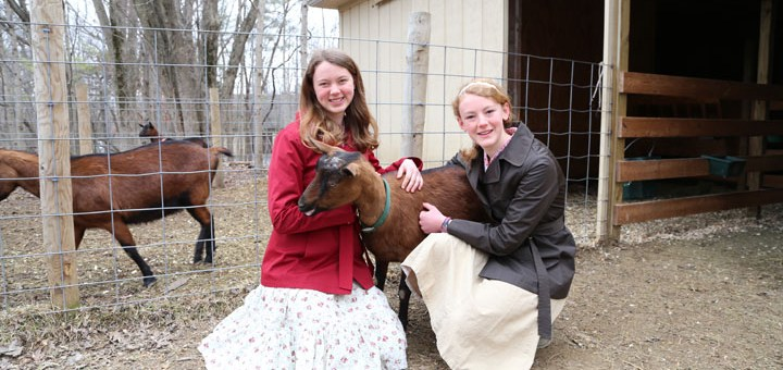 Deirdre (left) and Ragan Kelley pet Fern, one of the Oberhasli goats that produces milk for the products made at Wildflower farm. (Photo by Ann Ma- rie Shambaugh)