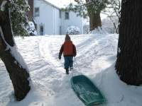 boy pulling sled in snow