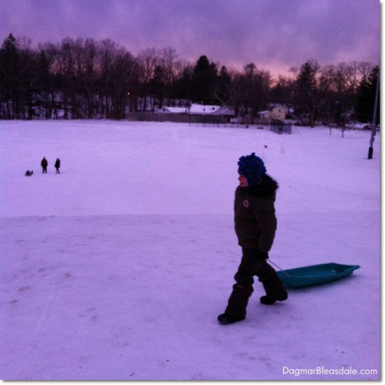boy with sled on top of sledding hill at sunset