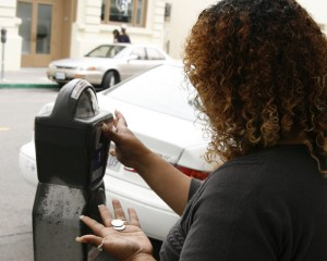 Rocio Soto pays a meter for parking in the Downtown area on Friday. Downtown parking fees could rise by 25 cents per hour in July.