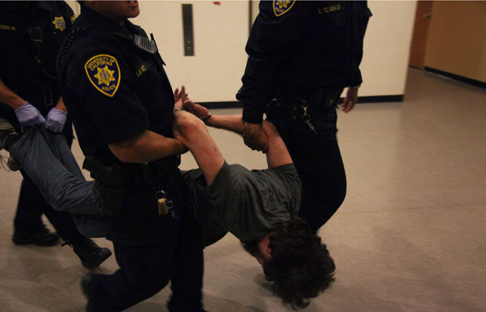 A protester is carried away by police after being arrested inside Tolman Hall.