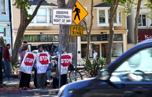 People demonstrating the lack of pedestrian safety measures on the corner of Dwight Way and Telegraph Avenue.