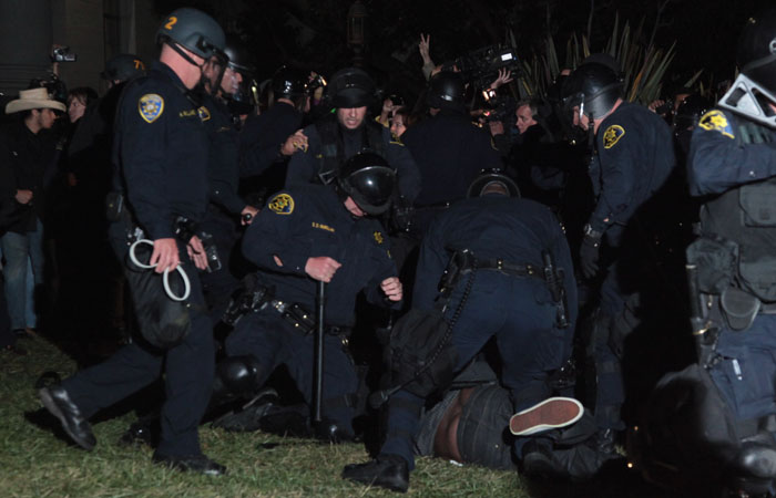 A protester is brought to the ground by police in front of Sproul Hall.