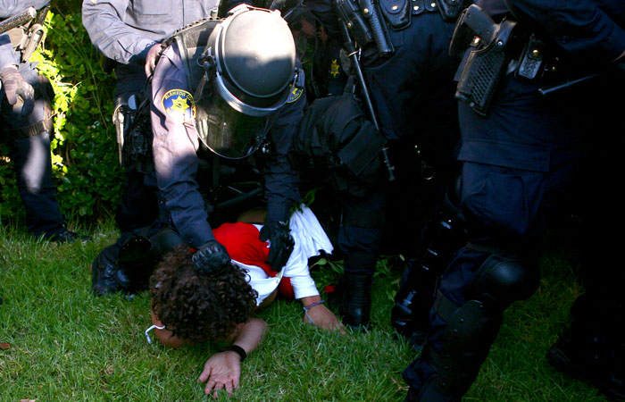 A protester is brought to the ground by a police officer in front of Sproul Hall.