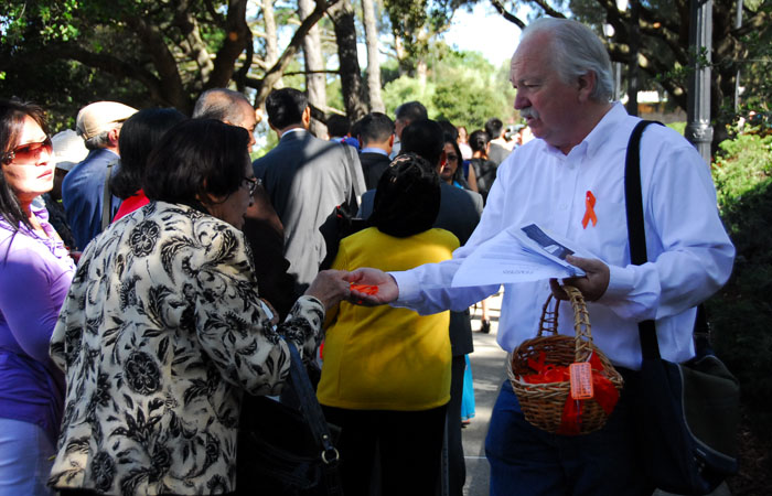 Protester hands out orange ribbons to attendees of the commencement ceremony.