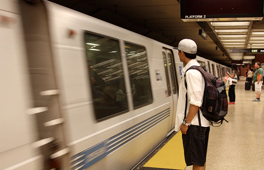 A man waits in the Downtown Berkeley BART station as a train approaches.