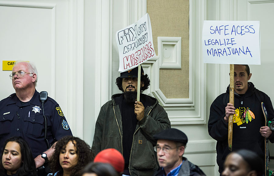 Protestors hold signs in opposition to the closing of Perfect Plants Patient's Group at Tuesday night's Berkeley City Council meeting.