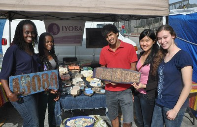 Anirudh Gupta, Yosha Huang and Jasmine Segall, three members of Berkeley microfinance pose with Efiya Asabi in front of her business stand in the Ashby Flea Market.