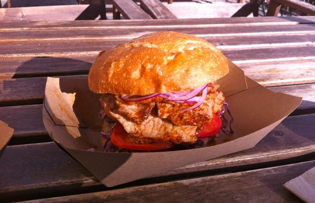 Chicharron sandwich - seasoned pork with crunchy red onion and cabbage between hot, buttery buns.