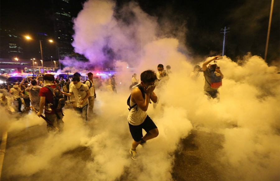 Demonstrators run from smoke during a protests in Hong Kong. In recent days, protests have rocked the city as civilians take to the streets to push for democratic changes.