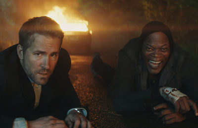 Ryan Reynolds, protecting Samuel Jackson, crawl away from a burning car.
