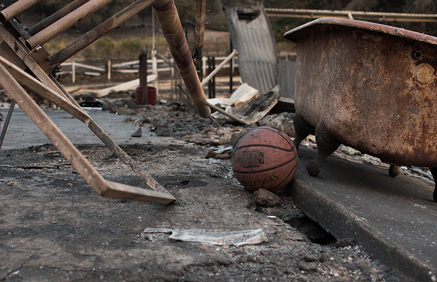 A basketball scorched by the fire lies next to a bathtub and fallen basketball hoop.