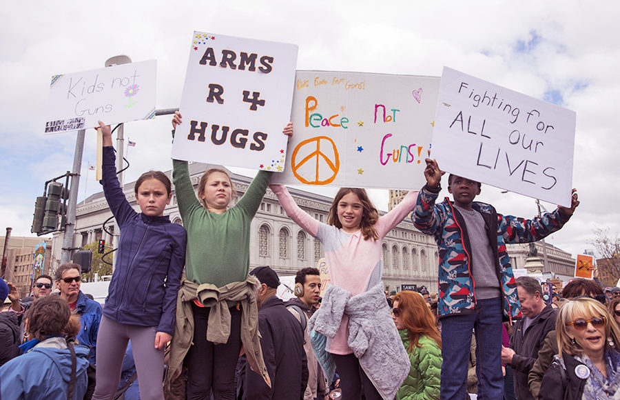 Protesters hold signs that criticize current gun control policies.