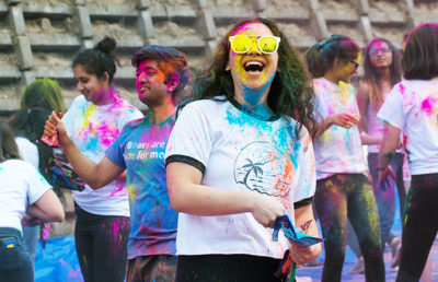 Attendee laughs while using the powder from color packets sold by the Indian Students Association.
